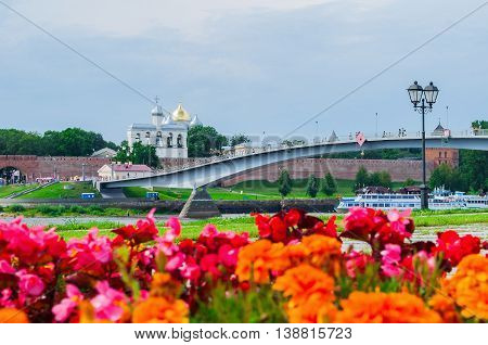 VELIKY NOVGOROD RUSSIA - JULY 15 2016. Novgorod Kremlin and footbridge across the Volkhov river in summer sunny day with flowerbed at the foreground. Selective focus at the Kremlin