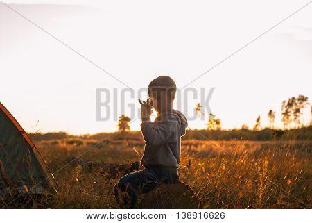 boy drinking juice at sunset boy sitting near tent silhouette shooting