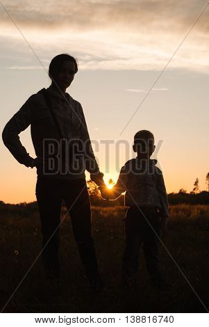 Silhouette of mother and baby at sunset the boy holds his mother's hand
