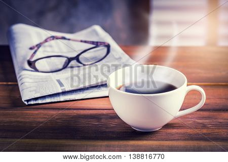 Coffee cup with newspaper and glasses in background on wooden table. Vintage tone photo with sunlight filter effect.