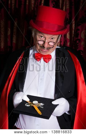 Unhappy magician on stage looking sad at a broken watch
