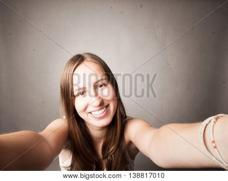 young girl taking a selfie on a gray background