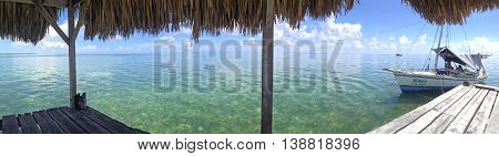 CAYE CAULKER BELIZE - OCTOBER 11 2015: Pier and boat on the background of the Caribbean sea. Panorama of several frames