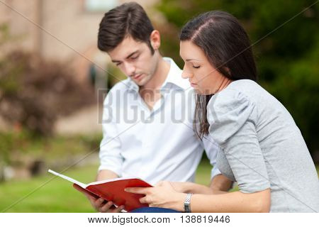 Two students reading a book on a bench in the park