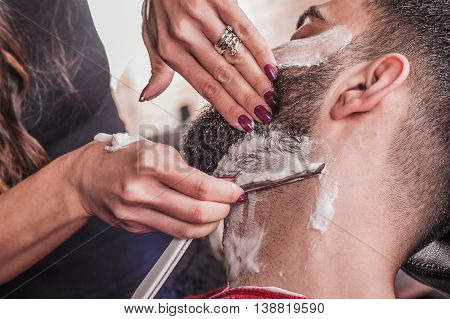 Female Barber Shaving A Client