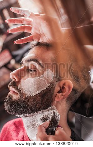 Female Barber With Shaving Brush Applied Foam To Face Of Client