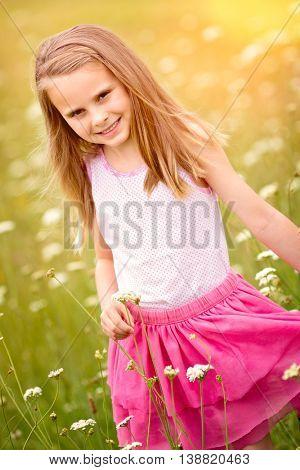 Pretty little girl picking flowers