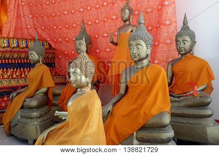 six life size Buddha statues with orange wraps in Buddhist temple near Ranot, Thailand, orange cloth hanging behind them, decorated podium edge seen behind statues