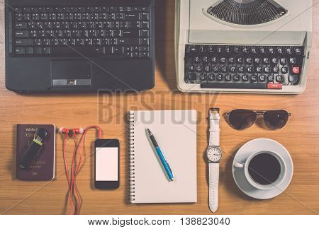 Office Desk With Computer, Supplies, Coffee Cup, Passport, Sunglasses And Wristwatch.