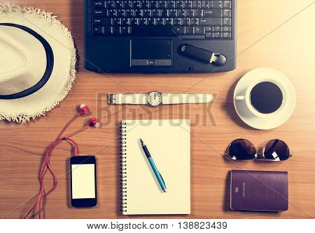 Office Desk With Computer, Supplies, Coffee Cup, Passport, Sunglasses, Hat And Wristwatch.