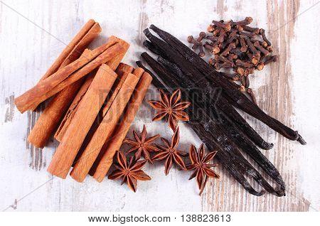 Cinnamon Sticks, Vanilla, Star Anise And Cloves On Wooden Surface