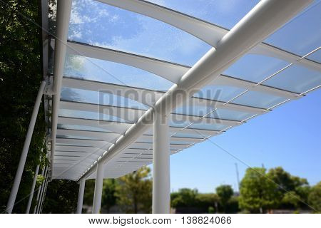 Outdoor transparent roof for walkway that can see bright blue sky.