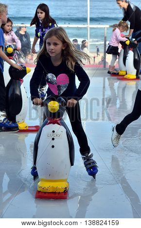 Sydney Australia - Jul 17 2016. A girl ice skating with a Penguin Skate Aid on Bondi ice rink. Australia's only beachside ice rink is on Bondi beach.