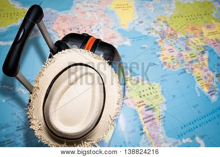 Traveling Bag With Straw Hat On The World Map