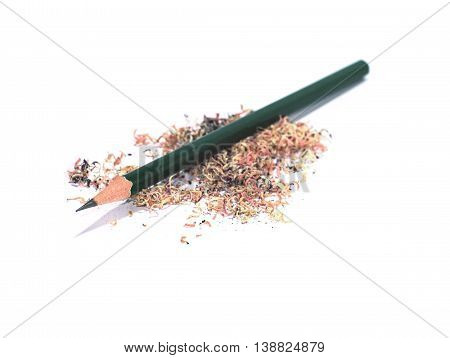 sharpened green pencil on a pile of pencil sawdust isolated on white background