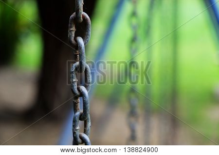 Old rusty chain of wooden swing in playground