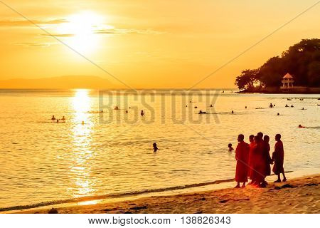 Orange robed buddhist monks on the beach as the sunset turns the sky and water orange in Cambodia