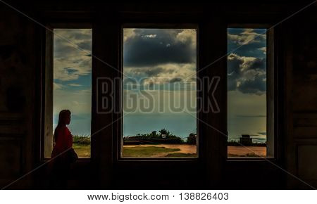 A woman gazes at the sea through a window in Cambodia