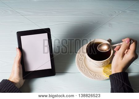 Female hands hold e-book on blue wooden background.