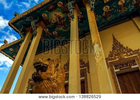 Lion statue and painted ceiling of a crumbling golden buddhist temple in Cambodia