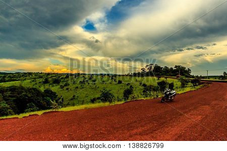 A motorbike parked on a red dirt road through rolling green hills under an orange and blue sky after sunset in the Cambodian countryside