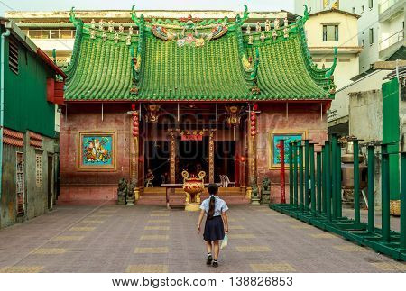 A shoolgirl walks to Chinese temple in Phnom Penh, Cambodia
