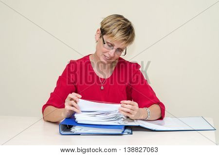 Business Woman Sitting At A Table, Carefully Studying The Documents Folder