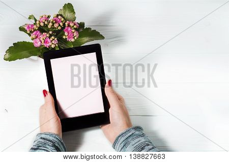 Female hand with red nails holding e-reader on blue wooden background. Modern book reading. Woman reading e-book.