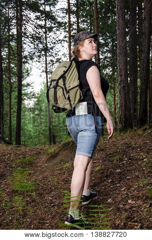 Beautiful girl traveling in the forest with backpack and map. Adventure travel tourism hike concept.