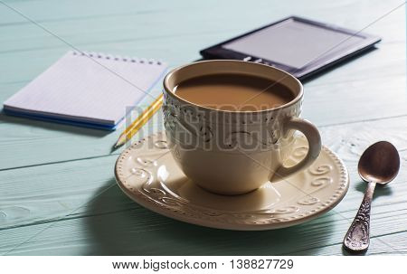 A cup of hot coffee with milk a notebook with a pencil and e-book on a blue wooden background.