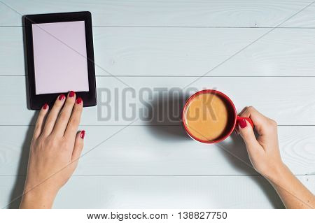 Female sitting, reading e-book and hands hold cup of coffee on blue wooden background, flat lay.