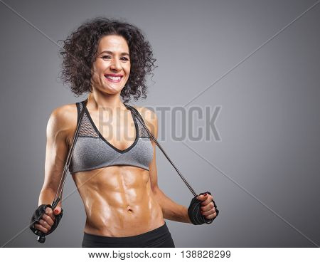 Happy smiling fit woman posing with a jumping rope on grey background