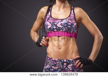 Image of a fit woman with a jumping rope on black background