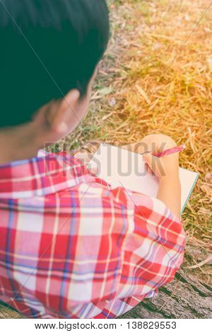 Back View. Boy Writing On Book. Education Concept. Vintage Style.