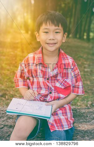 Happy Asian Boy Smiling And Holding A Book. Education Concept. Vintage Style.