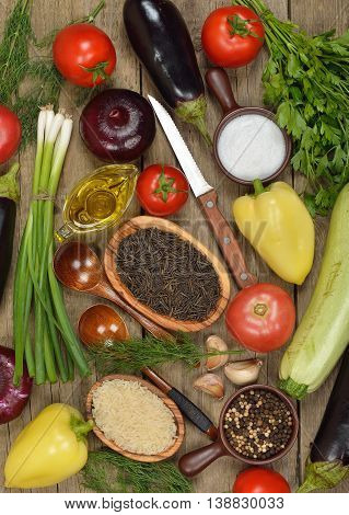 Raw rice and various vegetables on a wooden background vegetarian cooking concept