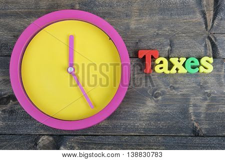 Taxes word on wooden table