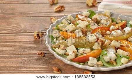 Salad with caramelized pear peach and blue cheese on a wooden background
