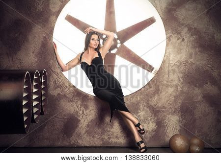 Elegant and beautiful top model near ventilation pipes posing with huge turbo ventilator behind her were lights coming trough.