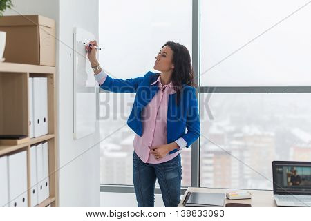 Young woman planning writing day plan on white board, holding marker in right hand.