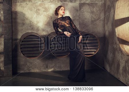 young girl in black vintage dress staing near ventilation pipes. proudly and thoughtfully looks aside.