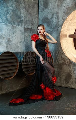 young girl in black vintage dress posing near ventilation pipes. proudly and thoughtfully looks aside.