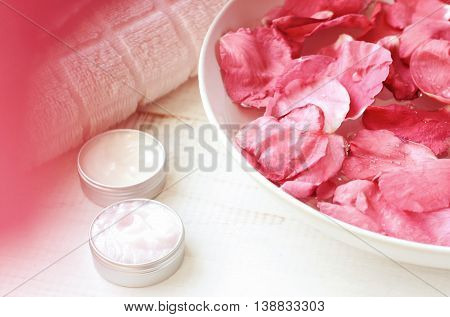Pink rose petals in bowl, cosmetic moisturizer emollient in containers, white towel, pink natural blur, creamy tones