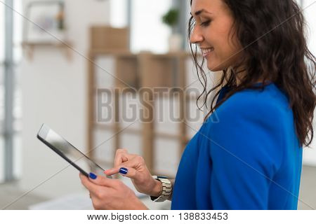 Portrait of an office manager holding her tablet, typing, using wi-fi internet and applications touching the pda screen