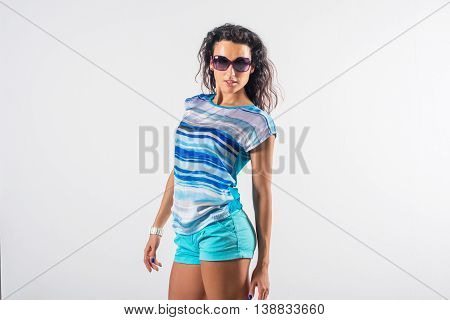 Studio portrait of a playful girl having fun, wearing sunglasses and trendy summer outfit
