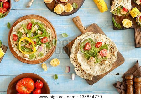 Outdoors Food Concept. Tortilla with grilled chicken fillet and grilled vegetables on a wooden table outdoors. Top view