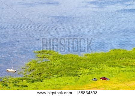 Bright top view of the lake coast with tourists