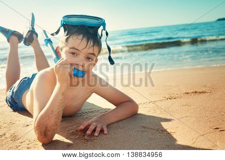 Child lying on the beach with swimming mask and flippers. Boy on vacation at sea