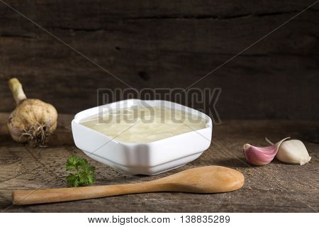 Fresh garlic dip sauce in white bowl over old rustic wooden background