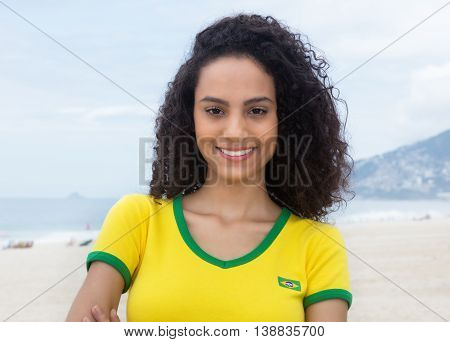 Laughing brazilian sports fan with curly hair at Copacabana beach in the summer